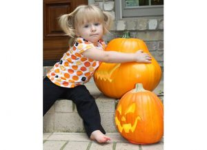 girl hugging pumpkin