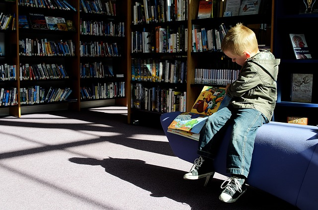 kid reading at library