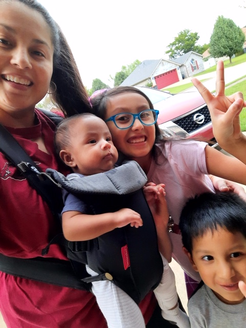 Erika Rodriguez standing with her three children in their neighborhood