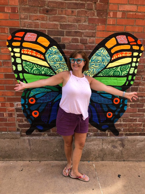 Melanie Hewins in front of butterfly mural.
